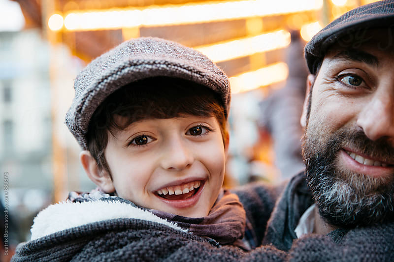Father and son in front of golden carousel lights by Beatrix Boros for Stocksy United