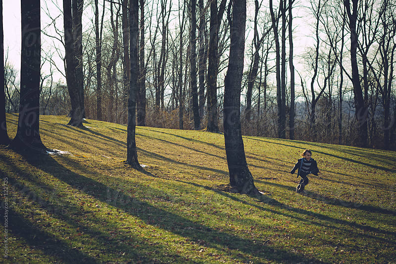 Young Boy Running Through a Park by Kevin Keller for Stocksy United
