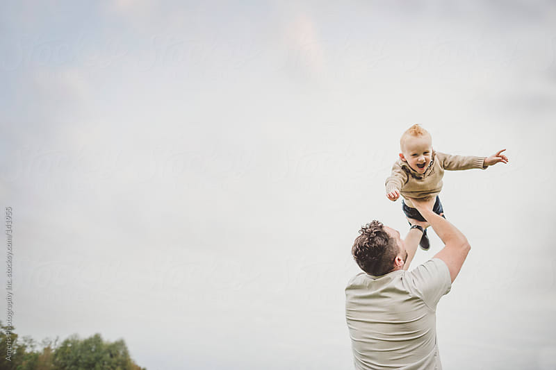 Dad throwing young son up in the air by Rob and Julia Campbell for Stocksy United