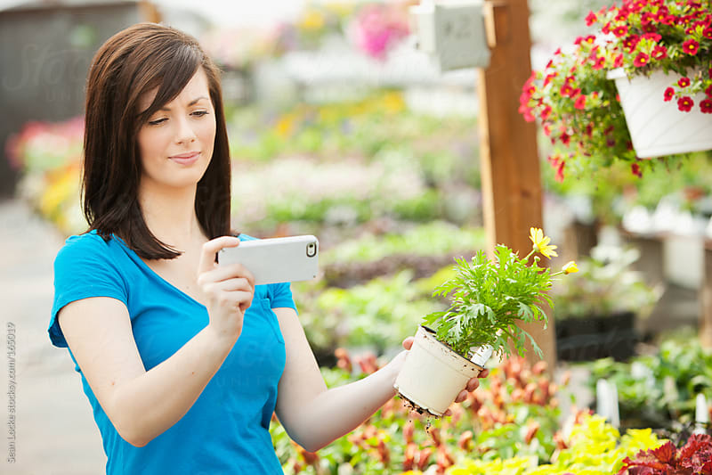 Nursery: Woman Reading Information on Flower by Sean Locke for Stocksy United