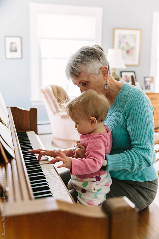 Grandmother playing Piano with Infant by Raymond Forbes LLC for Stocksy United