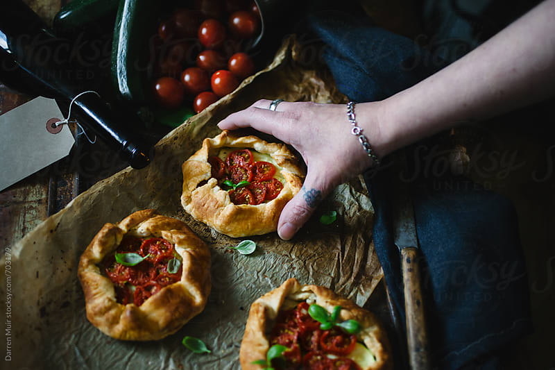 Woman's hand reaches for a freshly baked vegetarian pastry. by Darren Muir for Stocksy United