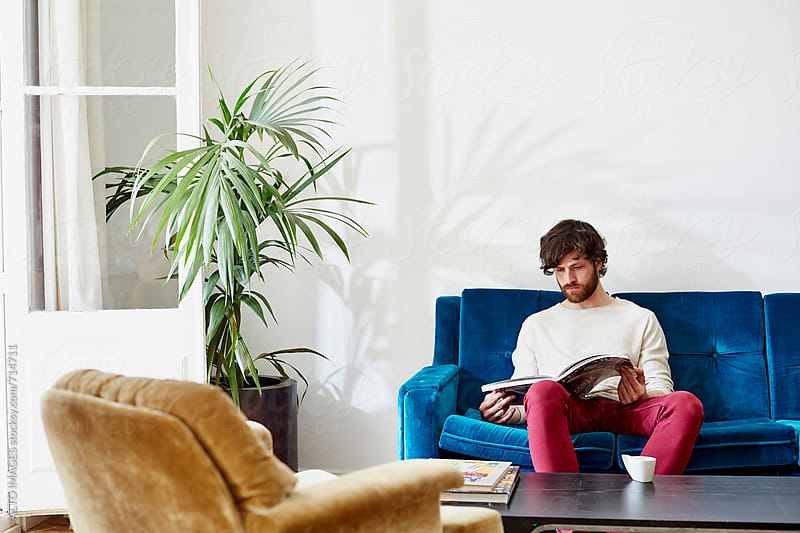 Man Reading Magazine In Living Room by ALTO IMAGES for Stocksy United