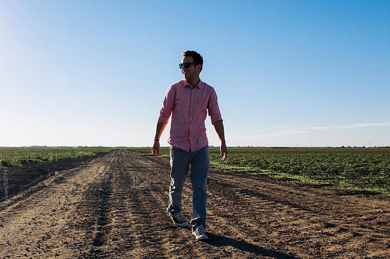 Man Walking on Dirt Road by Stephen Morris for Stocksy United