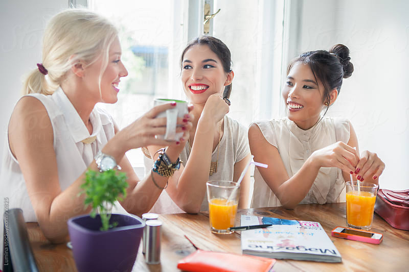 Smiling Women Chatting at a Cafe by Lumina for Stocksy United