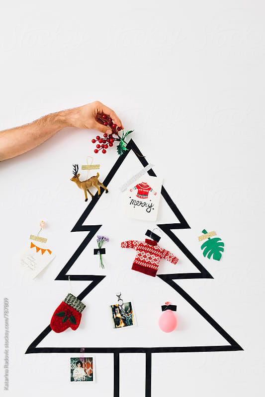 Male Hand Putting Mistletoe on a Top of the Christmas Tree by Katarina Radovic for Stocksy United