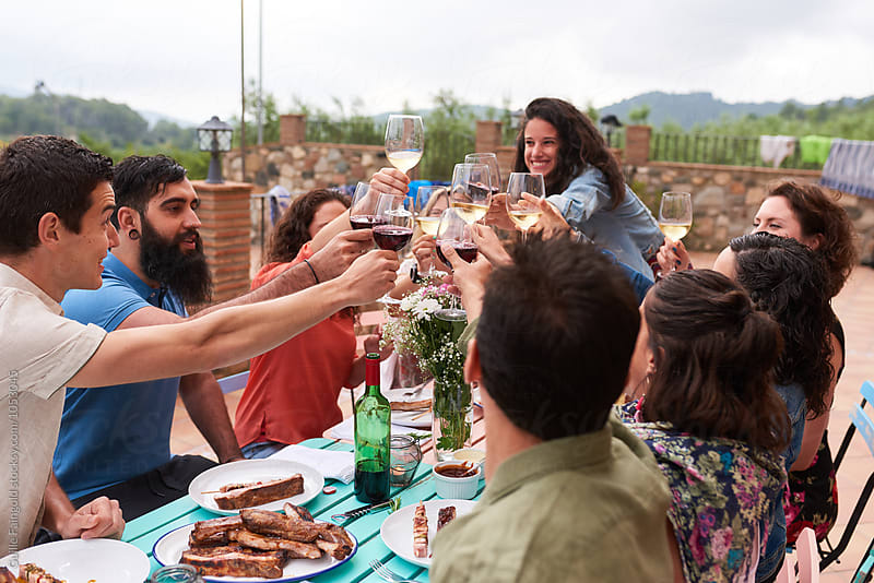 Group of smiling friends toasting with glasses by Guille Faingold for Stocksy United