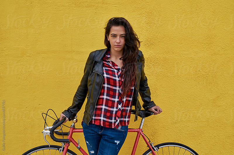 Young woman standing in front her bicycle on a yellow wall by Guille Faingold for Stocksy United
