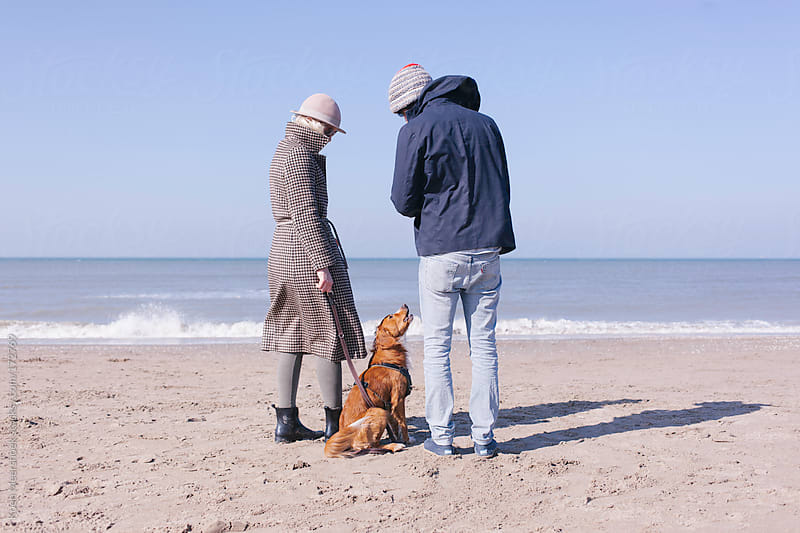 A couple standing on the beach with their dog. by Koen Meershoek for Stocksy United