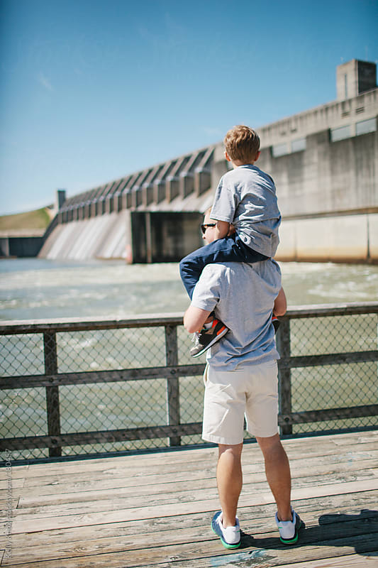 father and son sightseeing at a river dam by Kelly Knox for Stocksy United