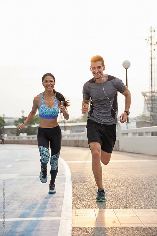 Couple running together in the city by Jovo Jovanovic for Stocksy United