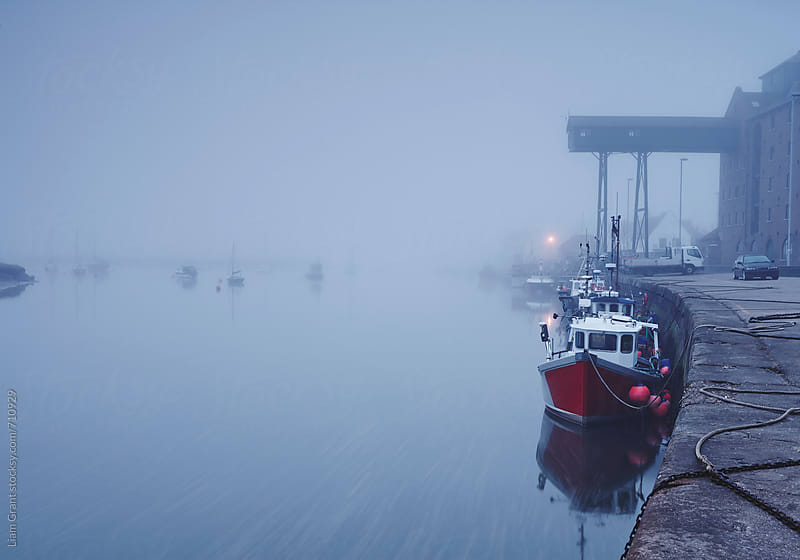 Fishing boats moored in the harbour in fog at dawn. Wells-next-the-sea, Norfolk, UK. by Liam Grant for Stocksy United