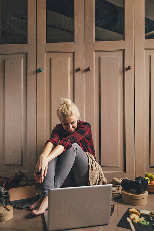 Happy Blonde Woman Sitting on the Floor and Watching a Movie by Lumina for Stocksy United