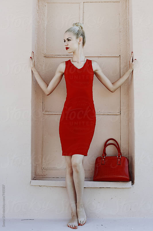 Blonde girl in a red dress by Svetlana Shchemeleva for Stocksy United