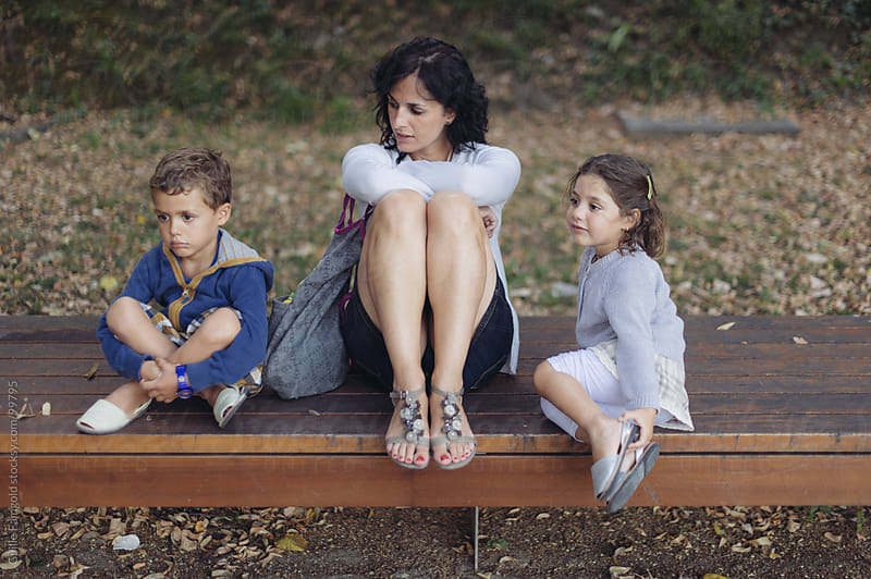 Mother and two kids on bench. by Guille Faingold for Stocksy United
