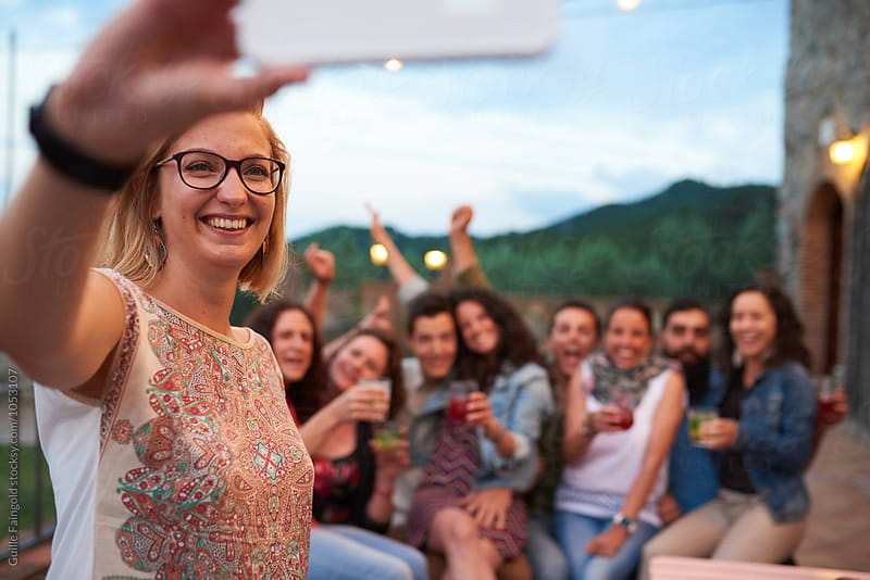 Smiling blonde person taking group selfie of friends at terrace by Guille Faingold for Stocksy United