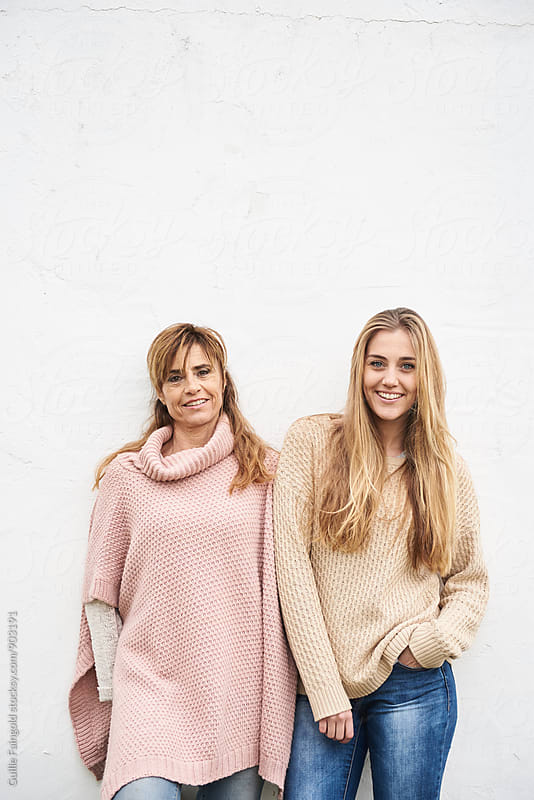 Mother and daughter standing against white wall by Guille Faingold for Stocksy United