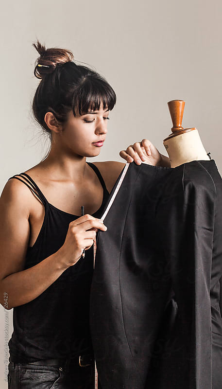 Young Fashion Designer taking measures of textile on mannequin by Audrey Shtecinjo for Stocksy United