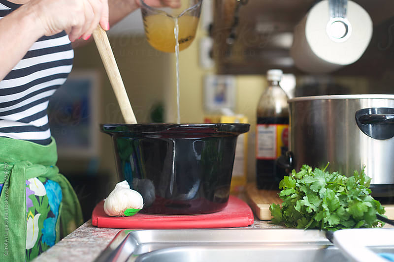 Woman pouring ingredients into a slow cooker by Carolyn Lagattuta for Stocksy United
