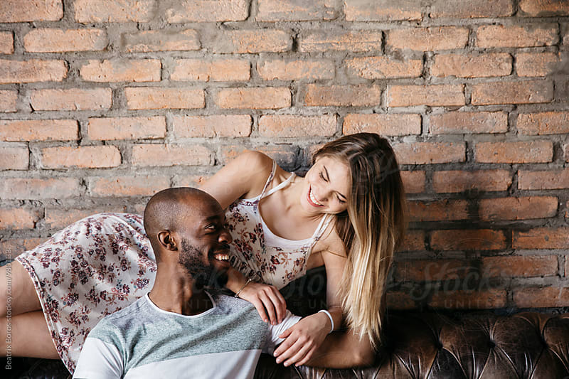 Happy multi-ethnic couple talking to each other in front of a brick wall on a leather sofa by Beatrix Boros for Stocksy United