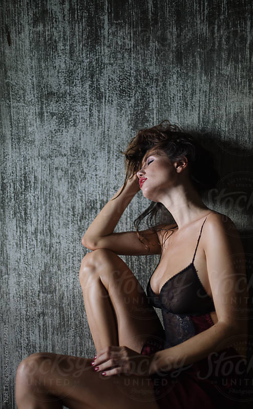 Sensual beautiful woman in black underwear leaning on the dark grey wall by Nabi Tang for Stocksy United