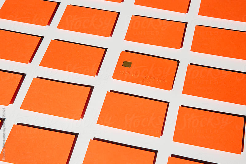 One orange blank credit card in a rectangle shaped background by Beatrix Boros for Stocksy United