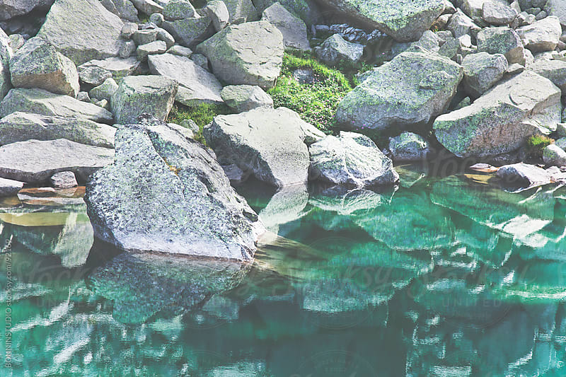 Reflection of rock in a lake.  by BONNINSTUDIO for Stocksy United