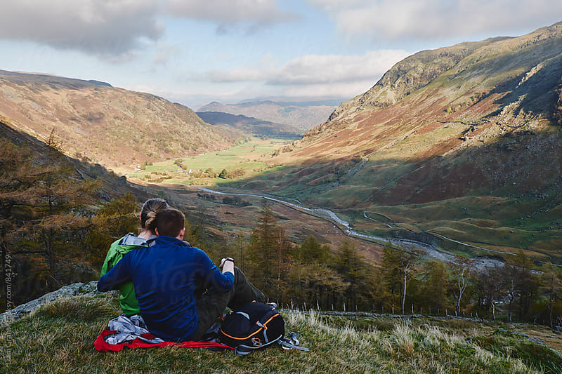 Young couple sat admiring the mountain view. Cumbria, UK. by Liam Grant for Stocksy United