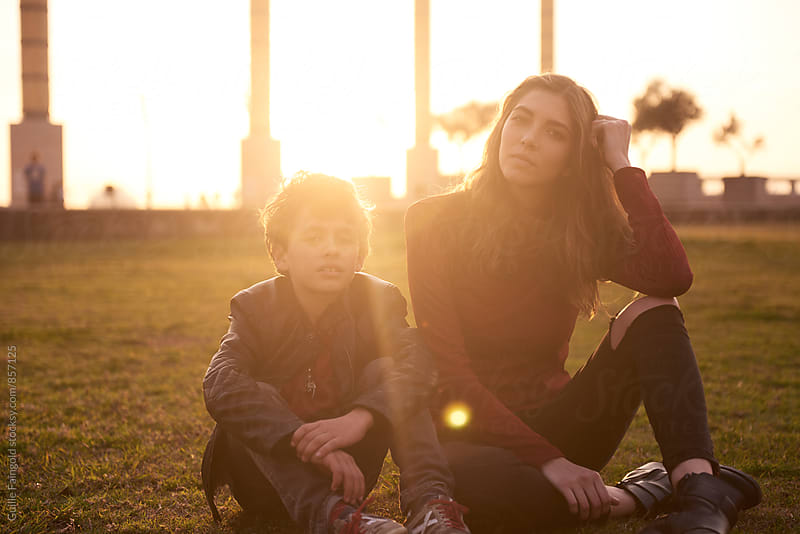 Portrait of sister and brother sitting on grass by Guille Faingold for Stocksy United