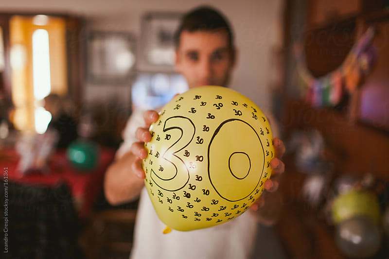 Man holding balloon with number 30 by Leandro Crespi for Stocksy United