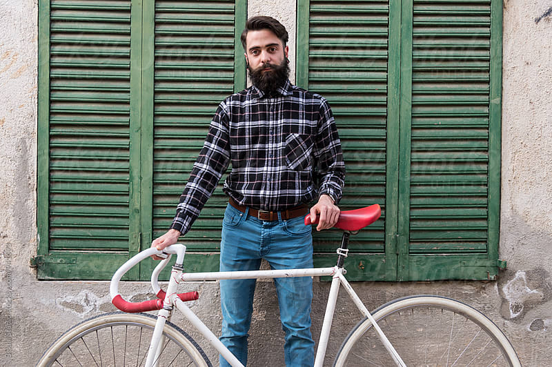 Portrait of young man with fixed gear bicycle by Bisual Studio for Stocksy United