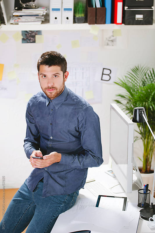 Young creative designer with smartphone standing in front of office by BONNINSTUDIO for Stocksy United