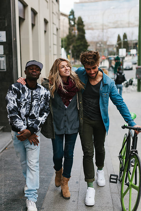Three Multi-Ethnic Friends Walking in the Street by VICTOR TORRES for Stocksy United