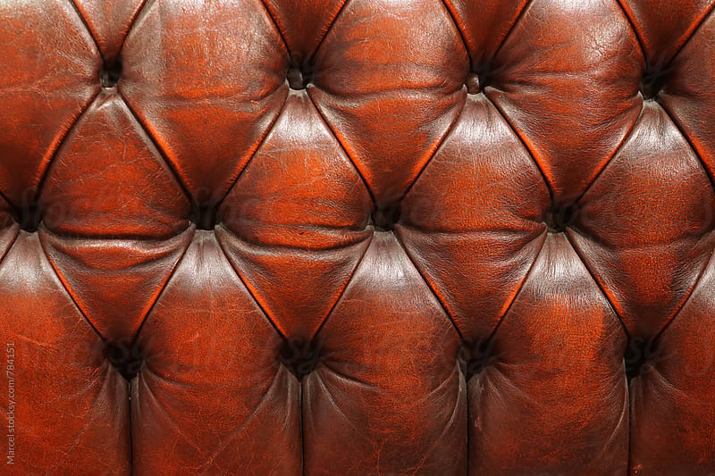 Red leather couch detail by Marcel for Stocksy United