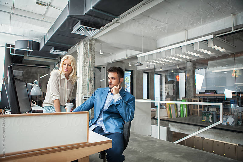 Businessman and Businesswoman Working in Their Modern Office by Lumina for Stocksy United