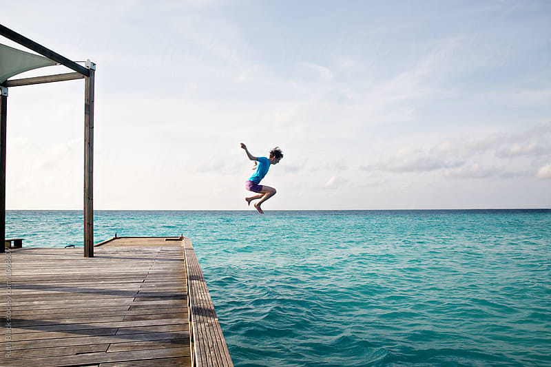 Teenage boy jumping off the jetty by Ruth Black for Stocksy United