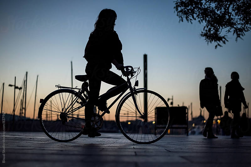 Young woman riding a bike in the port of Barcelona at sunset by Bisual Studio for Stocksy United
