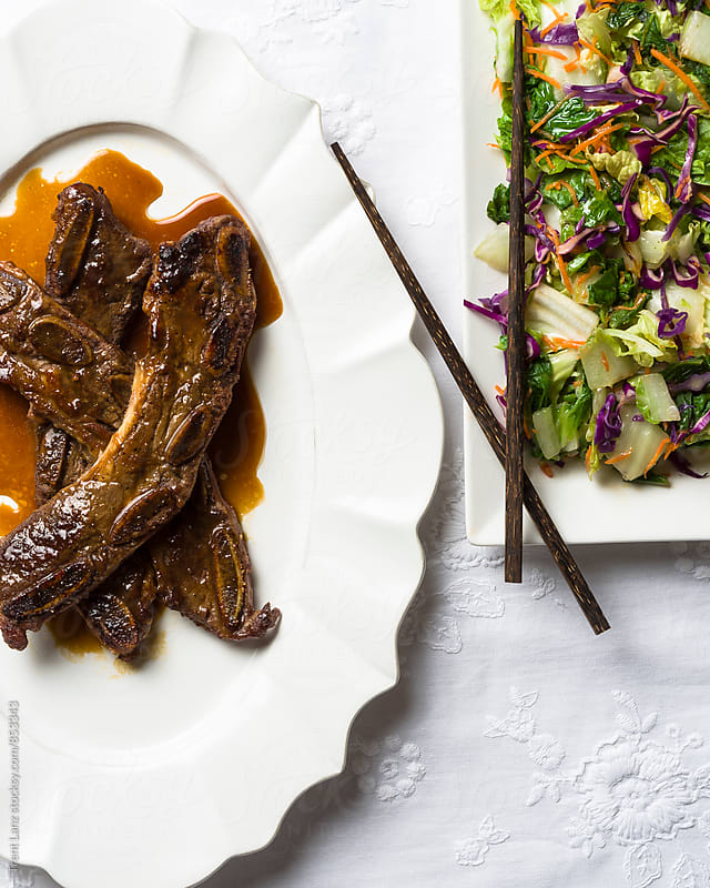 Delicious roasted juicy Korean short ribs and mixed salad by Trent Lanz for Stocksy United
