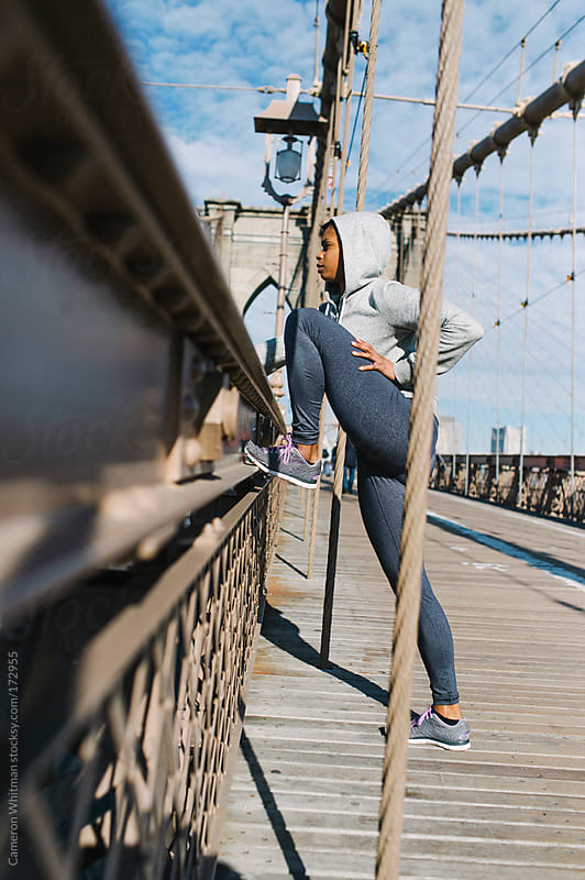 Young woman stretching during a run across the Brooklyn Bridge by Cameron Whitman for Stocksy United