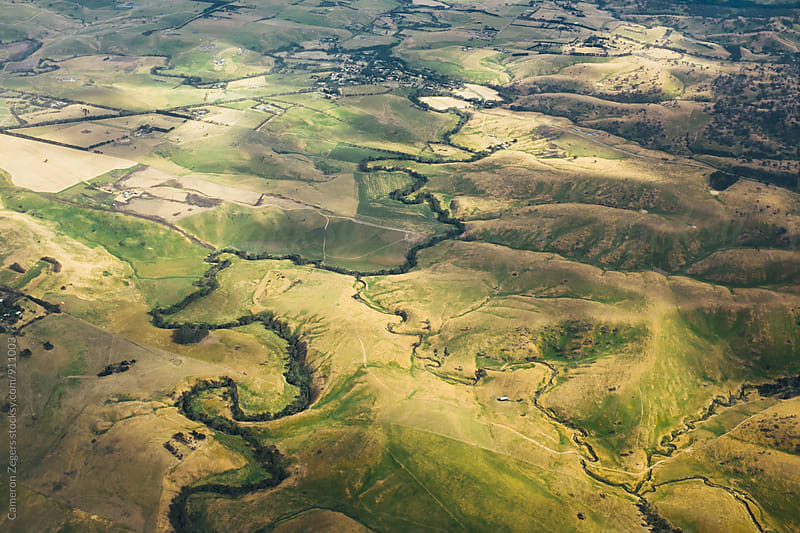 aerial view of stream winding through farmland by Cameron Zegers for Stocksy United