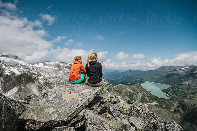two female hiking friends sitting in high alpine scenery overlooking the valley underneath by Leander Nardin for Stocksy United