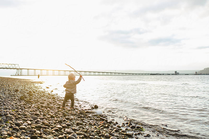 Little boy stands on the rocky shore holding a stick above his head by Amanda Voelker for Stocksy United