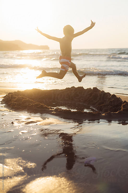 Child jumping at sunset by the sea by Dejan Ristovski for Stocksy United