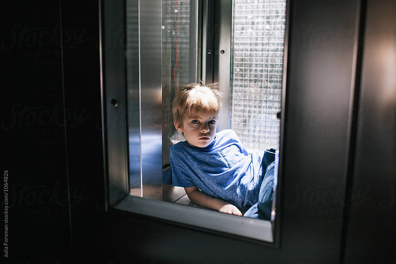 Young boy sits on the floor of an elevator. by Julia Forsman for Stocksy United