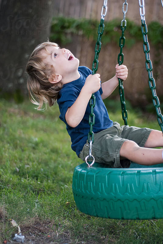 Child having fun on a tire swing in his backyard by Cara Dolan for Stocksy United