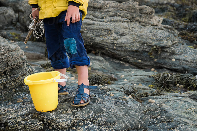 little child with patched pants and yellow bucket at sea side by Léa Jones for Stocksy United