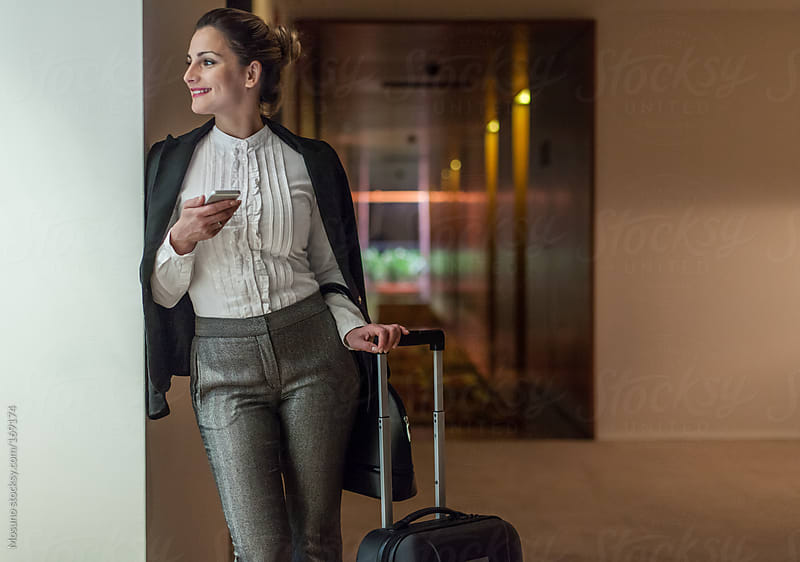 Businesswoman Waiting in a Hotel Hallway by Mosuno for Stocksy United
