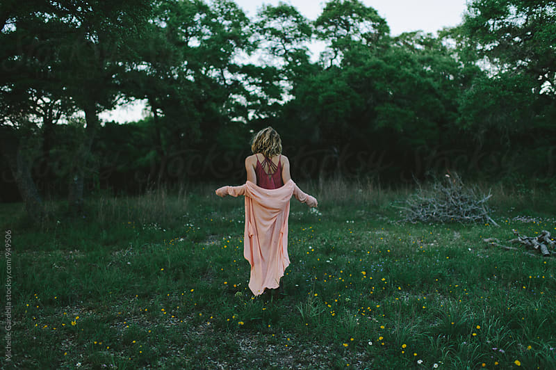 Young woman in flower field in TX by Michelle Gardella for Stocksy United