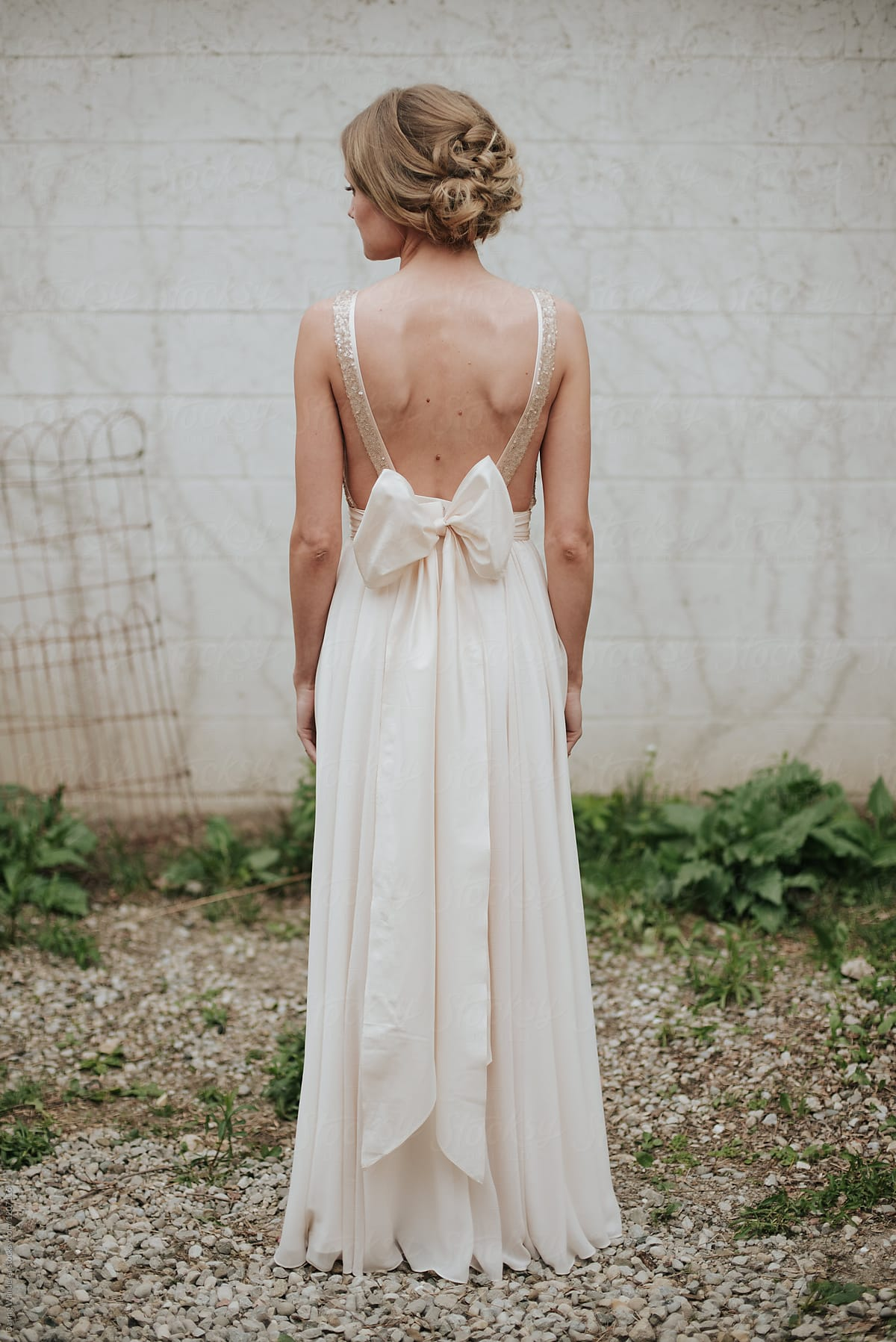 Delicate petite bride in simple minimalist wedding dress with large bow  sash by Jess Craven for Stocksy United