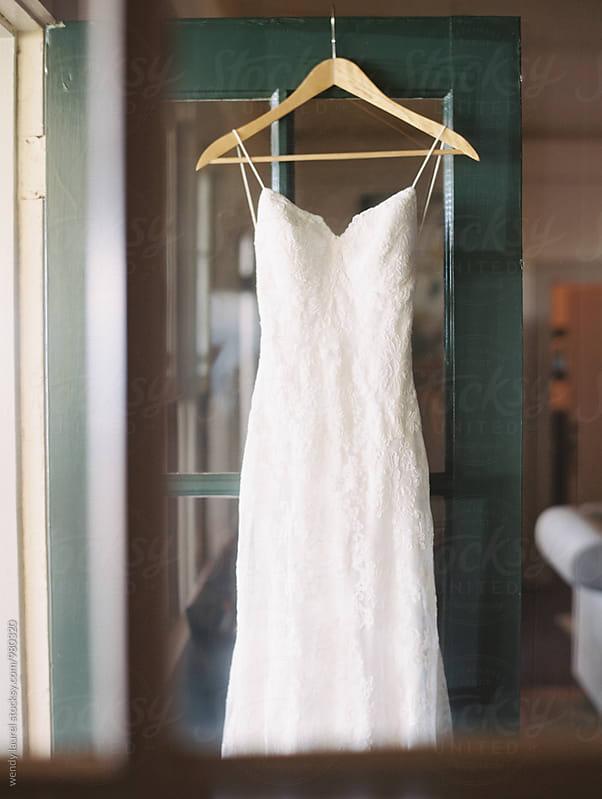 wedding dress on wooden hanger by wendy laurel for Stocksy United